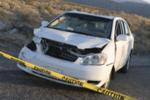 Warning tape across damaged car after wreck: RedLawList Accidents & Injuries Blog