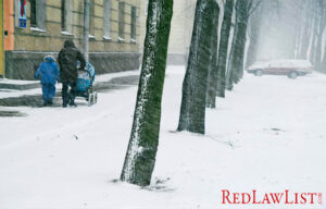 Mother and children walk on snowy sidewalk